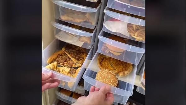 Για ποιο λόγο μια γυναίκα κρατάει πίτσες και μπέργκερ σε συρτάρια